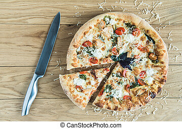 top view of italian pizza with knife on wooden tabletop