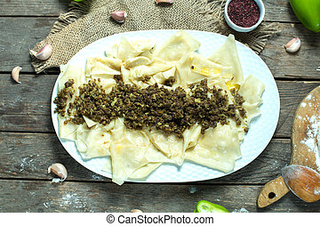 top view of khingal noodle sheets with fried minced meat on a plate on rustic background