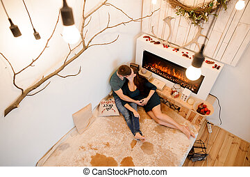 Top view of kissing pregnant couple lying near the burning fireplace
