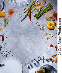 Top view of kitchen table with chili pepper, asparagus, salad pepper, corkscrew, mushrooms, garlic on a gray background.