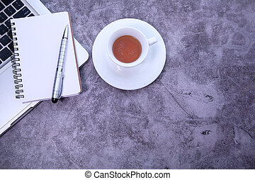Top view of laptop, notepad, tea with copy space.