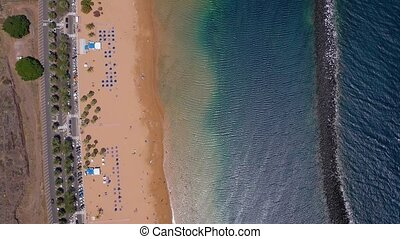 Top view of Las Teresitas beach, road, cars in the parking lot, golden sand beach and the Atlantic Ocean. Tenerife, Canary Islands, Spain