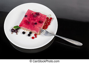 Top view of layered cake slice with berries on dish