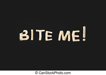 top view of lettering bite me made from cookie dough isolated on black