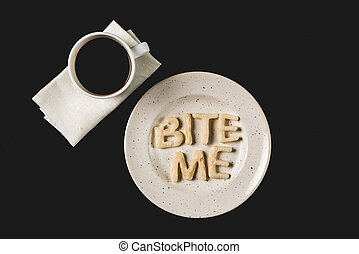 top view of lettering bite me made from cookie dough on plate with coffee cup isolated on black