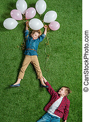 top view of little boy holding smiling girl with balloons on grass
