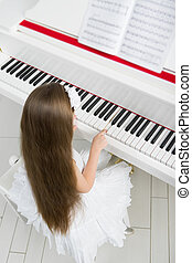 Top view of little child in white dress playing piano