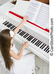 Top view of little girl in white dress playing piano