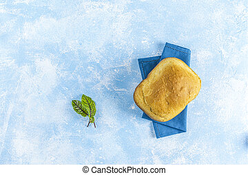 Top view of loaf of freshly baked bread with parsley on linen towel over light blue concrete background