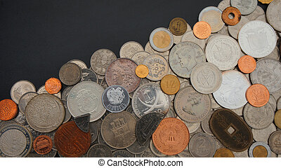 Top view of lot of coins of different countries of the world disordered on black table - Numismatics scene