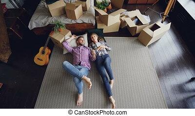Top view of loving couple lying on bedroom floor in new...