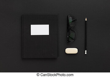 Top view of low key black office desk with notebook and glasses