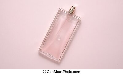 Top view of luxury bottle of perfume on pastel pink surface. Minimal composition. Flat lay. Top view.