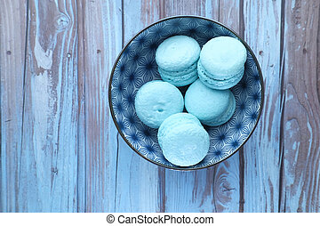 top view of macaroon in a bowl on wooden table