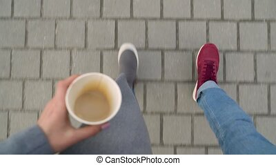 Top view of male and female legs strolling along the sidewalk. Woman drinking coffee