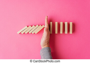 Top view of male hand interrupting collapsing dominos in a conceptual image of personal crisis solution. Over pink background with copy space.