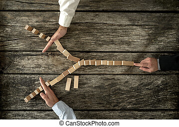 Top view of male hand pushing dominos placed in Y shape knocking them down and two other hands stopping them each on one side. Conceptual of crisis management in business.