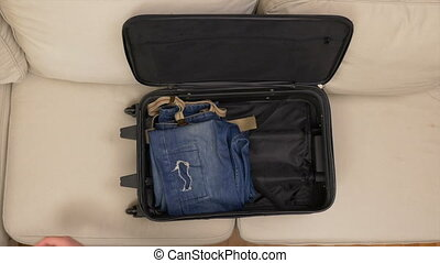 Top view of male hands packing clothes and preparing suitcase for travel