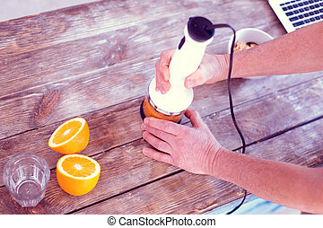 Top view of man caring about his diet using hand blender while making orange juice