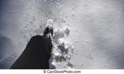 Top view of man legs stepping on deep snow illuminating sunlight. Unrecognizable hiker walking through snowy winter forest. Guy going outdoor. POV Slow motion Close up.