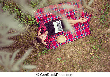 top view of man using a laptop computer under the tree