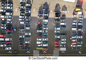 Top view of many cars parked on a parking lot.
