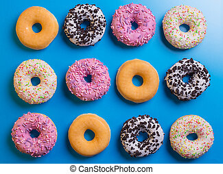 Top view of many colorful donuts on blue background.