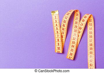 Top view of measuring tape on purple background. Tailor and slim waist concept with emty space for your idea