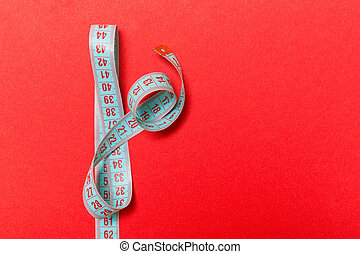 Top view of measuring tape on red background. Tailor and slim waist concept with emty space for your idea