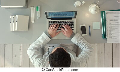 Top view of Medical worker with laptop. Doctors using keyboard at work