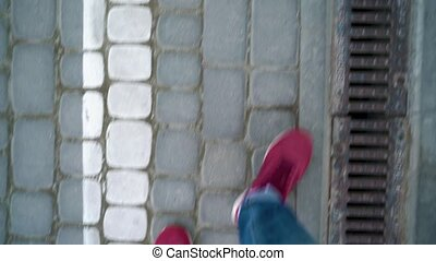 Top view of mens legs in red sneakers walking along the...