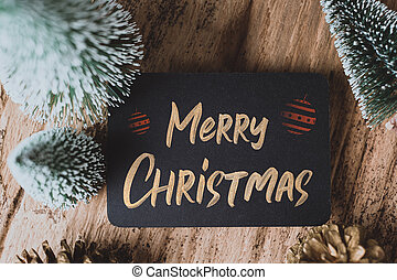 Top view of Merry Christmas and happy new year on blackboard with xmas tree and gold pine cone on grunge wood table .winter holiday greeting card.