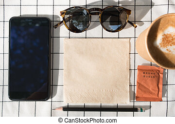 Top view of mobile phone with blank screen with coffee cup,brown sugar,sunglasses,pencil tissue paper on white table cloth.Mock up for display content.leisure lifestyle. clipping path screen.