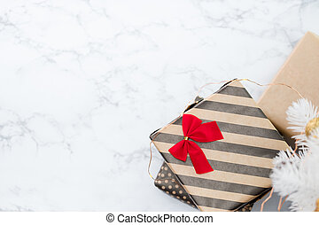 Top view of modern striped present box with red bow lay under white christmas tree on white marble floor, Holiday gift giving, leave space for adding text