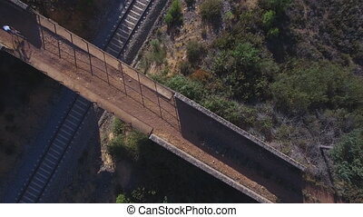 Top view of mountain bike cyclist over bridge and railway -...