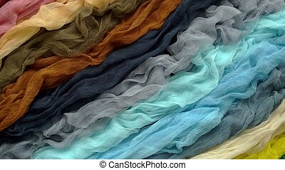 Top view of multi colored gauze fabric placed on a table. Flat lay. Trendy rainbow color background.