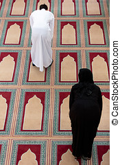 top view of Muslim man and woman praying in mosque.