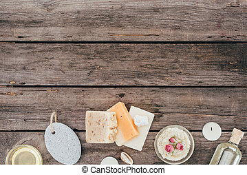 top view of natural soap, oil, salt scrub, pumice and spa treatment on wooden table