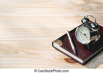 Top view of note book, pen and alarm clock on wooden table background with copy space for insert text.