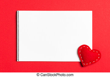 Top view of notebook surrounded with a textile heart on colorful background. Valentine's Day concept
