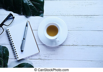 Top view of notepad with pen and tea on wooden table