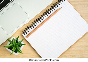 Top view of office desk with open spiral notebook on wood table
