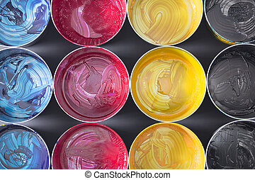 Top view of old CMYK paint cans on dark background. Colorful background.