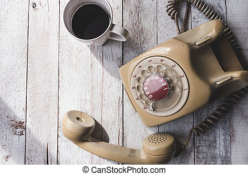 Top view of Old telephone with coffee cup on white wooden table background.