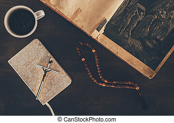 top view of open bible and rosary on wooden table