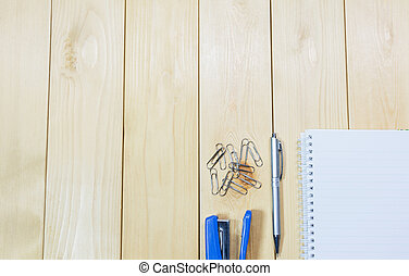 Top view of open book. Book, open with stapler and pen on wooden table background