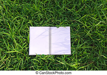Top view of open book on grass field background.