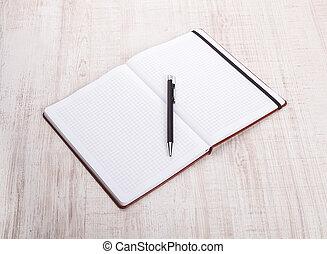 top view of open book with pen on wooden table