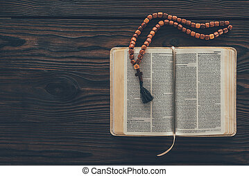top view of open holy bible with rosary on wooden table