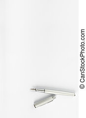 Top view of open ink pen lying on blank sheet of white paper